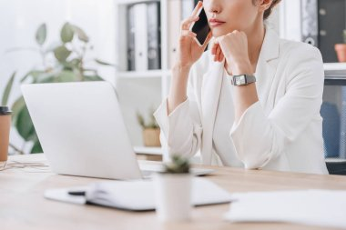 cropped view of frustrated businesswoman working with smartphone and laptop at workplace