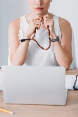 Cropped view of businesswoman praying with rosary beads and looking at laptop stock vector