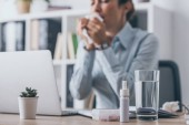 Fotografie medicines standing on worktable with blurred sneezing businesswoman sitting on background