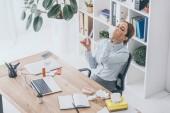 Erhöhte Ansicht von Kranken Erwachsenen geschäftsfrau Sprühen ihre Nase im Büro