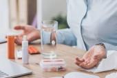 Fotografie Aufnahme von Kranken geschäftsfrau mit Medikamenten und Glas Wasser am Arbeitsplatz sitzen abgeschnitten