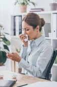 Fotografie sick adult businesswoman with runny nose using smartphone at office