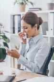 Fotografie Kranken Erwachsenen geschäftsfrau mit Schnupfen mit Smartphone im Büro
