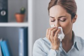 Fotografie close-up portrait of businesswoman with runny nose at office