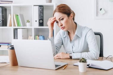 exhausted adult businesswoman with headache touching her head while sitting at office