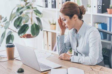 overworked adult businesswoman with headache sitting at workplace
