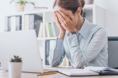 stressed adult businesswoman covering face with hands at office