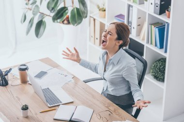 high angle view of stressed businesswoman screaming at workplace