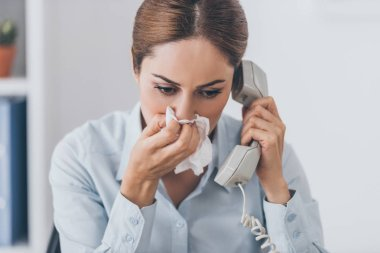 close-up portrait of adult businesswoman with runny nose talking by wired phone at office
