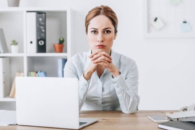 serious businesswoman sitting at workplace and looking at camera at office