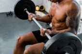 cropped shot of athletic young african american sportsman sitting on bench and lifting barbell in gym