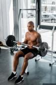 Fotografie Erhöhte Ansicht der athletische junge afrikanische amerikanische Sportler sitzen auf Bank und Aufhebung Langhantel im Fitness-Studio