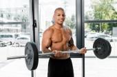 schöner muskulöser junger Sportler mit Langhantel und lächelnd in die Kamera im Fitnessstudio