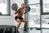 Fotografie svalnatý mladý afroamerické sportovec zvedání činka v posilovně