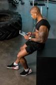 Fotografie Erhöhte Ansicht der jungen afrikanischen amerikanischen Sportler Kopfhörer mit digital-Tablette im Fitness-Studio