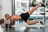 boční pohled na svalnatého afroamerické muže cvičení na fitness mat v tělocvičně