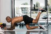 Fotografie Seitenansicht des muskulösen afrikanischen amerikanischen Mann auf Fitness Matte zu Fitness-Studio trainieren