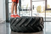 Photo cropped image of sportsman in sneakers standing on tire at gym