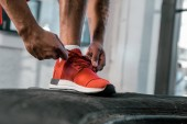 Photo cropped image of sportsman tying laces of red sneakers at gym