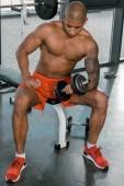 Fotografia sportsman afroamericano senza camicia muscolare che si esercita con il dumbbell alla palestra