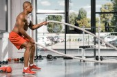 Fotografie side view of african american athlete working out with battle ropes at gym