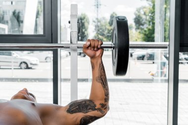 muscular tattooed african american sportsman lying on bench and lifting barbell in gym