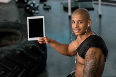 muscular young sportsman in earphones showing digital tablet with blank screen and smiling at camera in gym