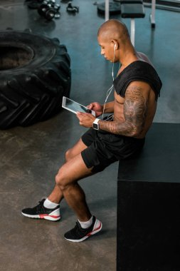 high angle view of young african american sportsman in earphones using digital tablet in gym
