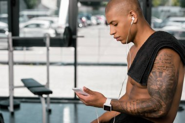side view of muscular shirtless young man in earphones sitting and using smartphone in gym
