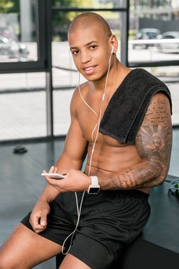 muscular young sportsman in earphones using smartphone and smiling at camera in gym