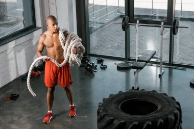 high angle view of african american sportsman with battle rope at gym