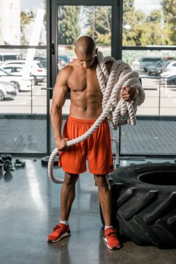 shirtless muscular african american man with battle rope at gym