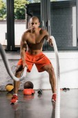 Fotografie muscular shirtless african american athlete working out with battle ropes at gym