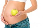 oříznutý pohled těhotné ženy dotýká břicho a hospodářství zelená apple izolované na bílém