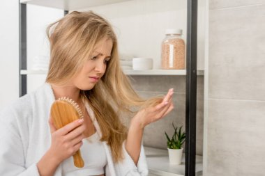 depressed pregnant woman with hair problems in bathroom