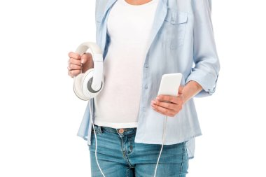 cropped view of pregnant woman holding headphones and smartphone isolated on white