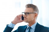 Photo handsome confident businessman in eyeglasses talking by smartphone and looking away in office