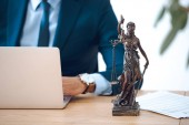 cropped shot of lawyer using laptop and lady justice statue on table