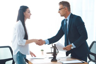 side view of professional lawyer and young female client shaking hands in office