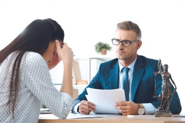 lawyer holding papers and working with upset client