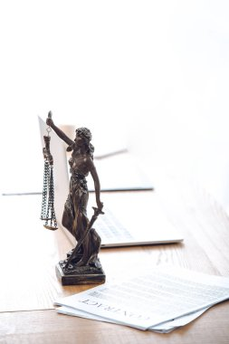 lady justice statue, contract and laptop computer on table