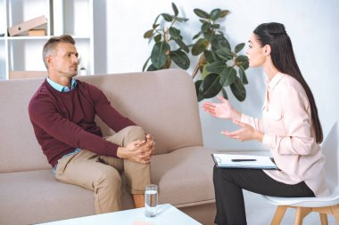 man and female psychologist talking during therapy session