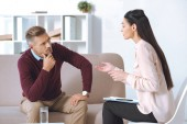 ženské psycholog mluví o pacienta na pohovce během sezení