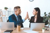 Fotografie portrait of business colleagues giving high five to each other at workplace with laptop in office