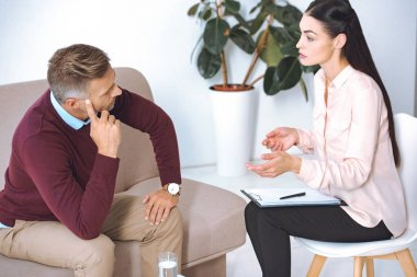 female psychologist talking on patient on sofa during therapy session