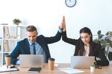 portrait of business colleagues giving high five to each other at workplace with laptop in office