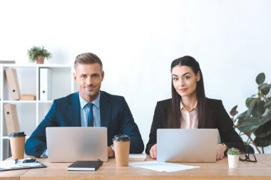 portrait of business colleagues at workplace with laptop in office