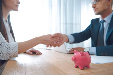 selective focus of insurance agent and client shaking hands at tabletop with pink piggy bank