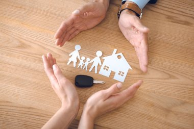 partial view of insurance agents and female hands with house, family paper models and car key on wooden tabletop