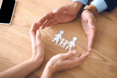 partial view of insurance agents and female hands with family paper model on wooden tabletop, family insurance concept